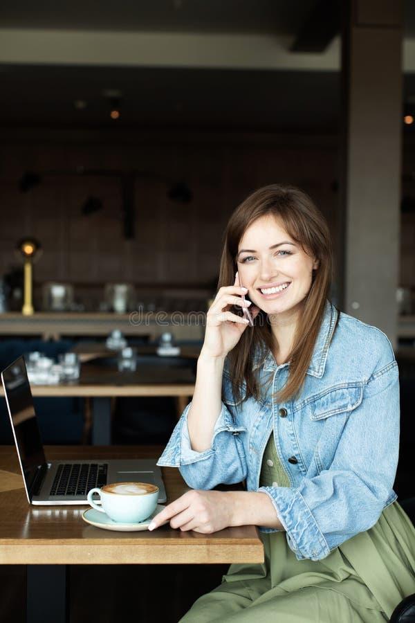 Ung flicka som dricker kaffe och talar på telefonen royaltyfri foto