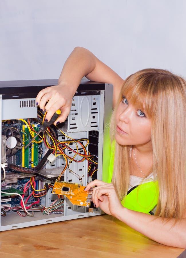 Ung flicka som fixar en dator arkivbild