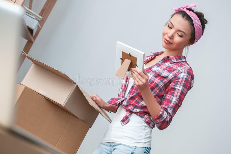 Ung flicka som flyttar sig till packande saker för nytt ställeanseende som ser fotoet som ler nostalgiker arkivbild
