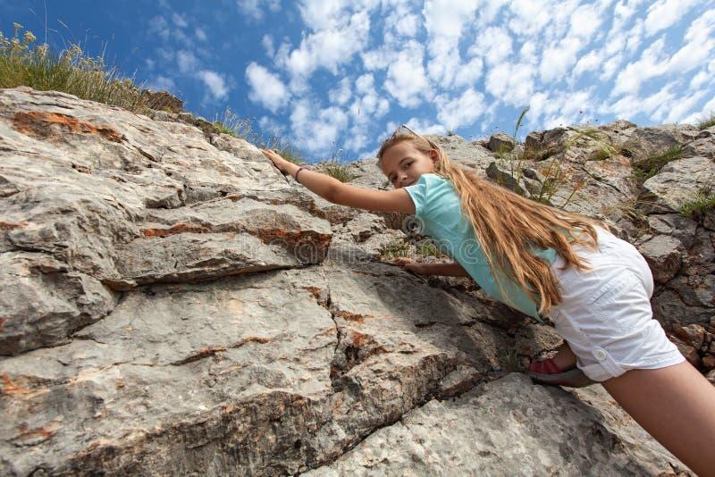 Ung flicka som fotvandrar - klättra upp en stenig lutning royaltyfri fotografi
