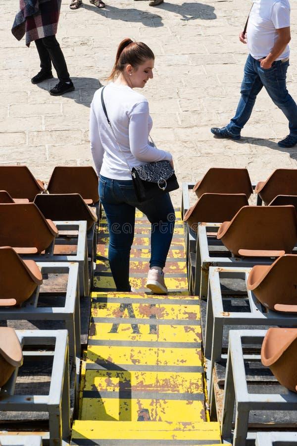Ung flicka som går ner stadionplatser i en stad med gul trappa Kvinna med den vita långa skjortan och handväskan i en byhändelse  royaltyfria bilder