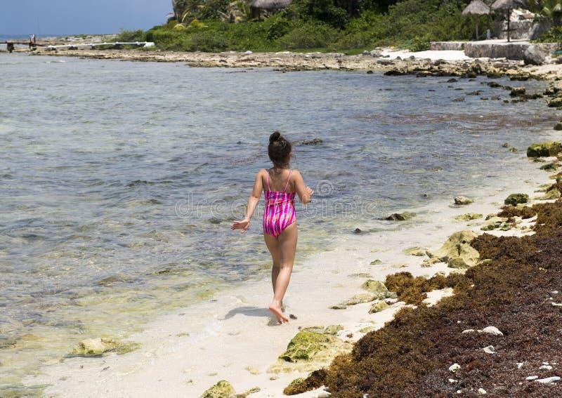 Ung flicka som går på stranden, Half Moon Bay, norr Akumal, Mexico fotografering för bildbyråer