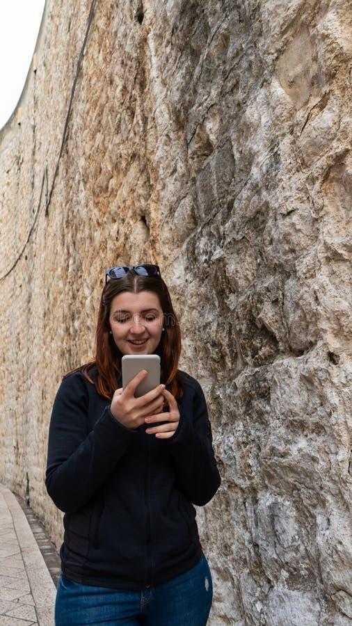 Ung flicka som går till och med forntida smala gator och skriver en smart telefon Härlig röd huvudkvinna som talar med hennes poj arkivbild