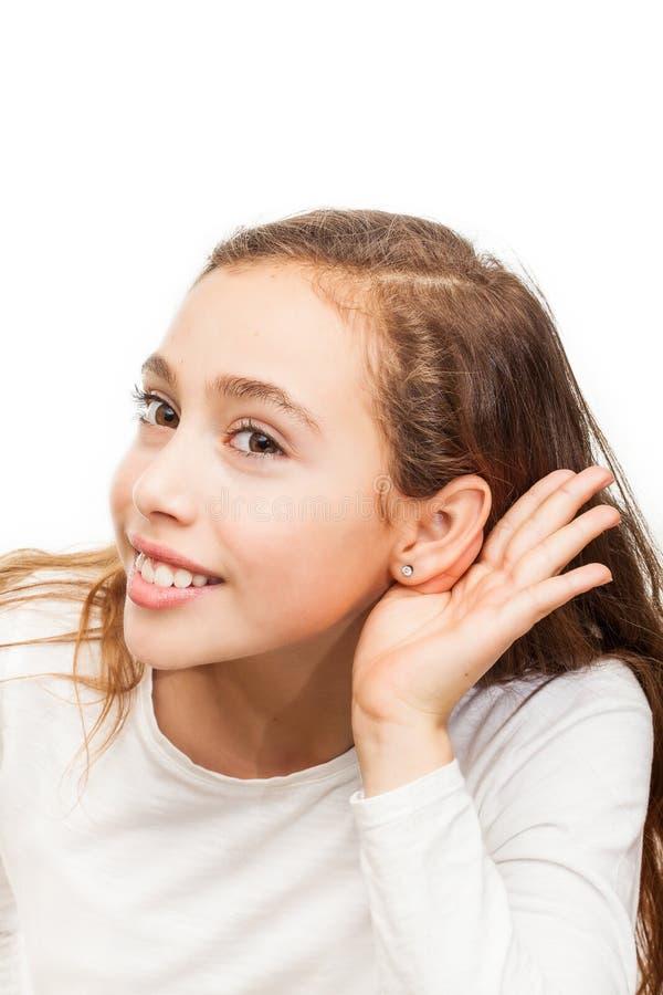 Ung flicka som gör en isolerad lyssnande gest royaltyfri foto