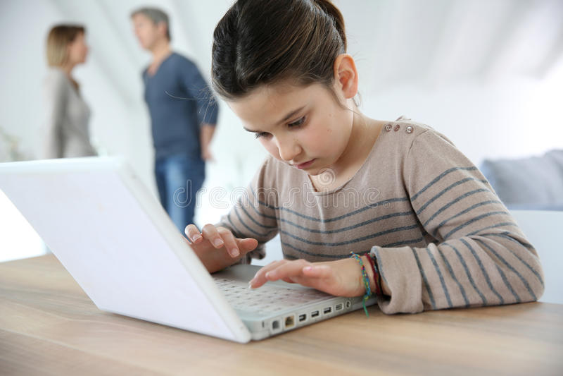 Ung flicka som gör läxa på bärbara datorn royaltyfri fotografi