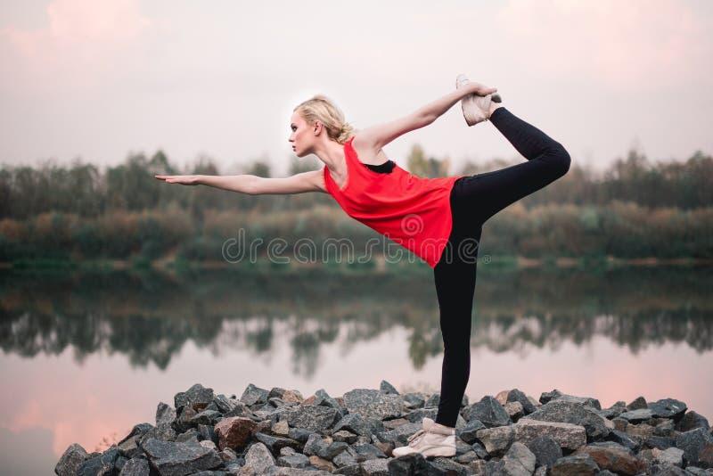 Ung flicka som gör landskap för flod för yogakonditionövning utomhus- near Aftonsolnedgången, Namaste Lotus poserar Meditationen  royaltyfri bild
