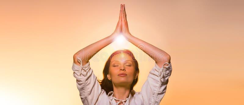 Ung flicka som gör yoga, orange himmelbakgrund royaltyfri bild