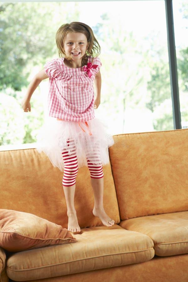 Ung flicka som har gyckel på soffan arkivbilder