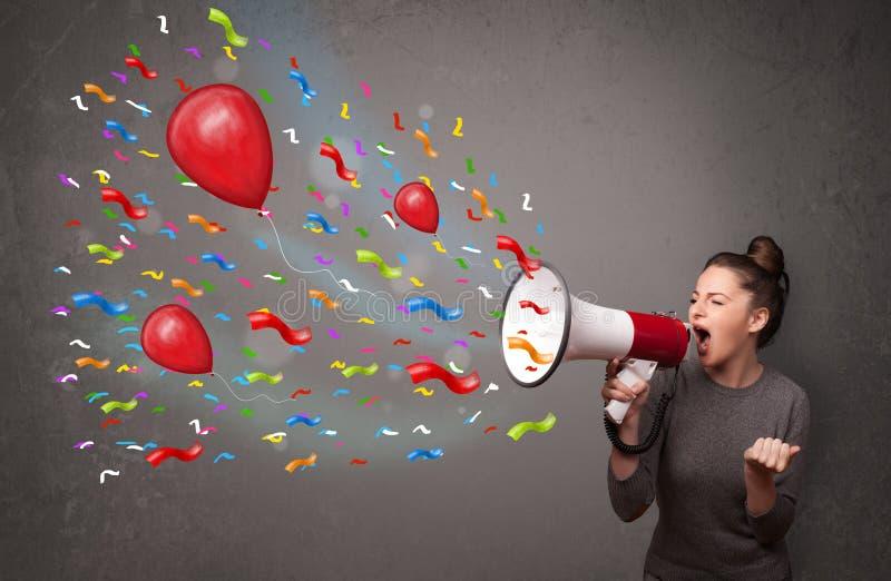 Ung flicka som har gyckel som ropar in i megafonen med ballonger royaltyfri foto