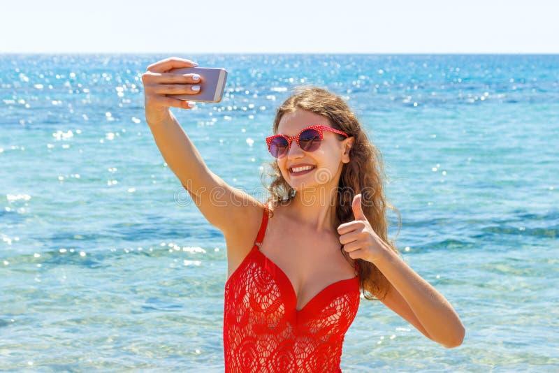 Ung flicka som har gyckel som tar smartphoneselfiebilder av henne Loppferier den lyckliga unga kvinnan som ger handtecknet, tumma arkivfoton