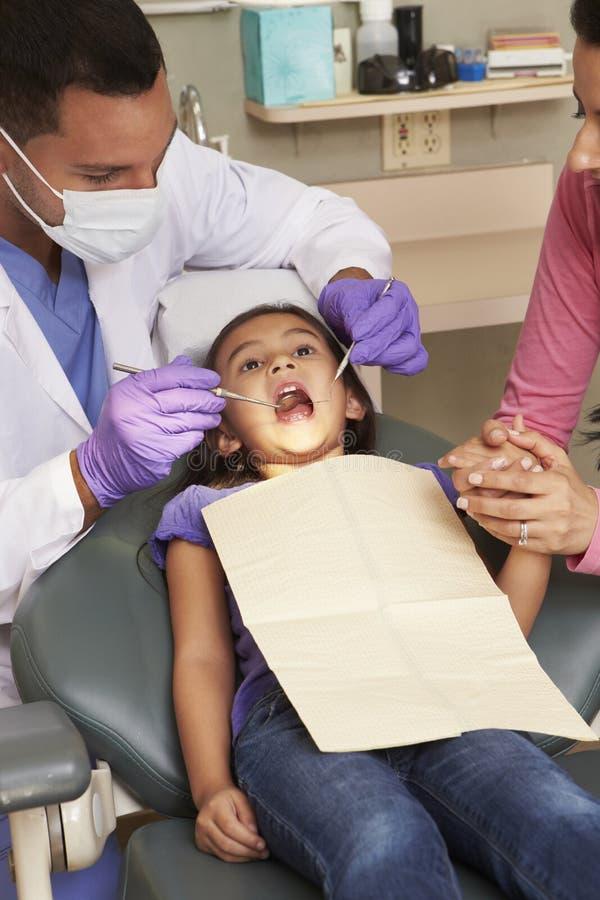 Ung flicka som har kontrollen upp på tandläkarekirurgi med modern arkivbild