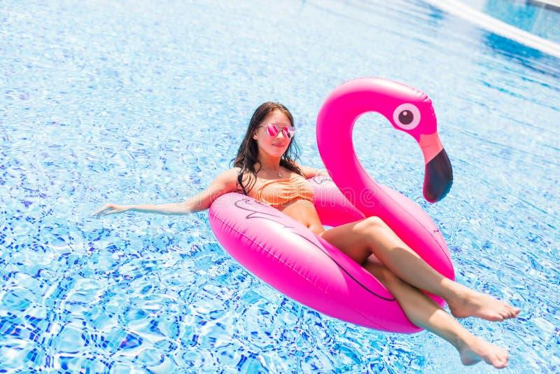 Ung flicka som har roligt och skrattar på en uppblåsbar jätte- rosa madrass för flamingopölflöte i en bikini Attraktiv brunbränd  royaltyfria foton