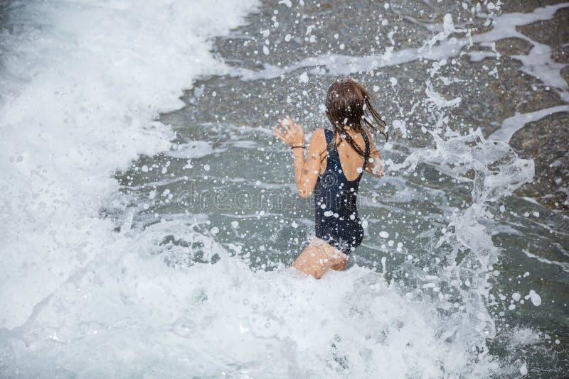 Ung flicka som hoppar i stora vågor med vatten som omkring plaskar royaltyfri bild