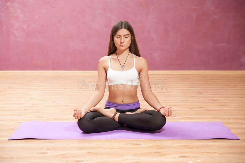 Ung flicka som inomhus gör yoga i lotusblommaposition fotografering för bildbyråer