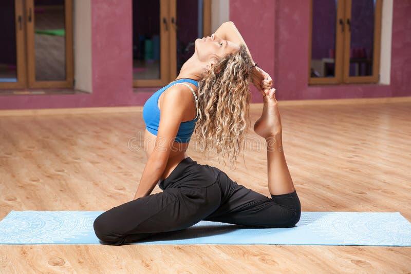 Ung flicka som inomhus gör yoga på mattt arkivfoto