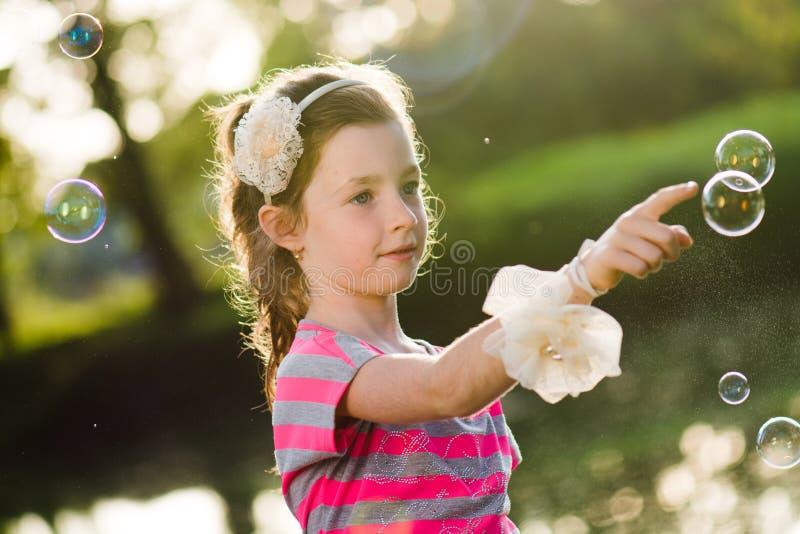 Ung flicka som jagar såpbubblor royaltyfria foton