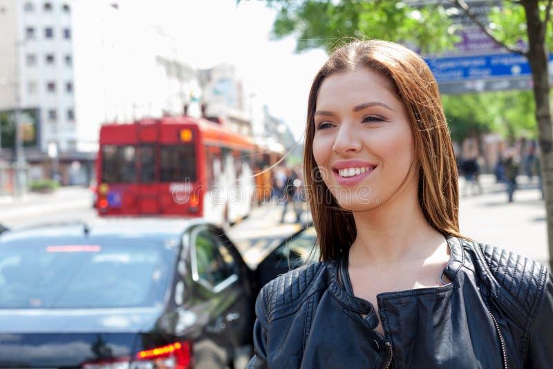Ung flicka som kallar en taxi i staden royaltyfria bilder