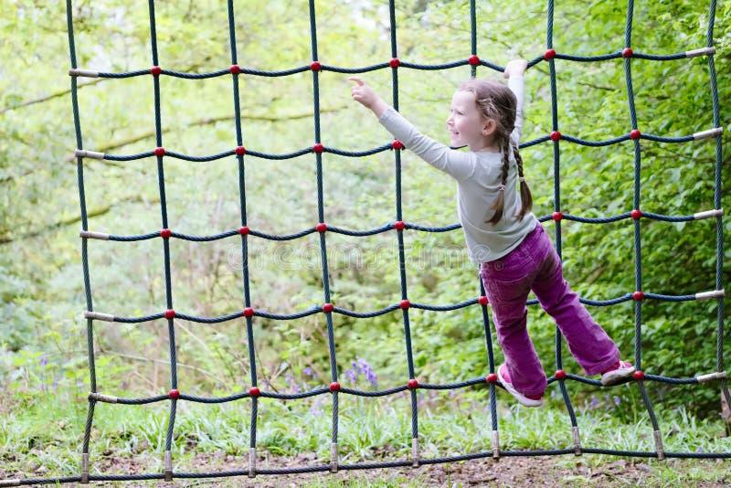 Ung flicka som klättrar på netto ram för rep i utomhus- skogsmarkaffärsföretagparkground royaltyfria foton