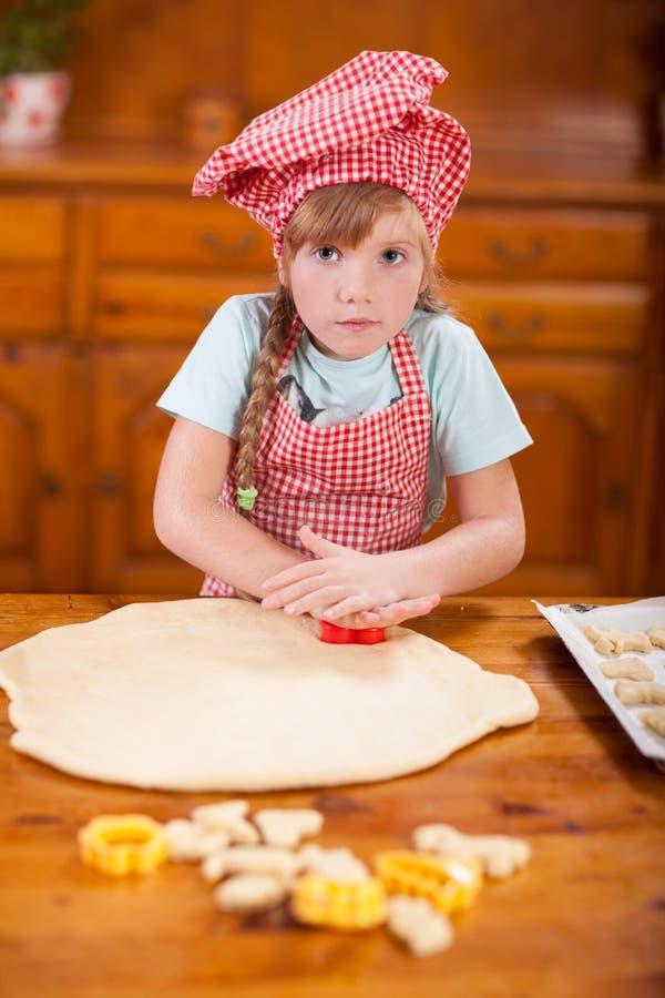 Ung flicka som knådar en deg för att göra kakor i köket arkivfoton