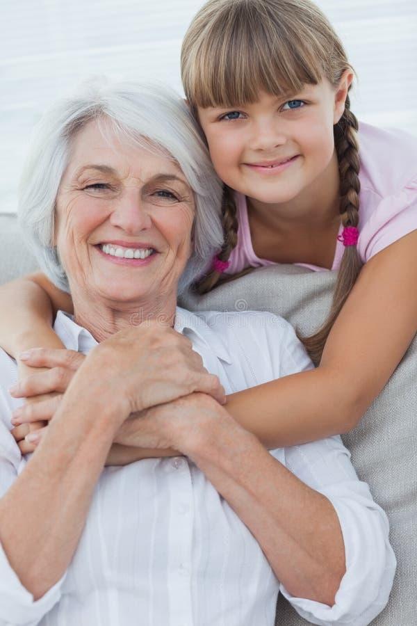 Ung flicka som kramar hennes farmor royaltyfri fotografi