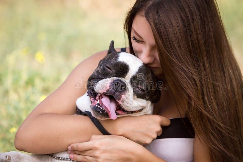 Ung flicka som kysser hennes hund arkivfoton