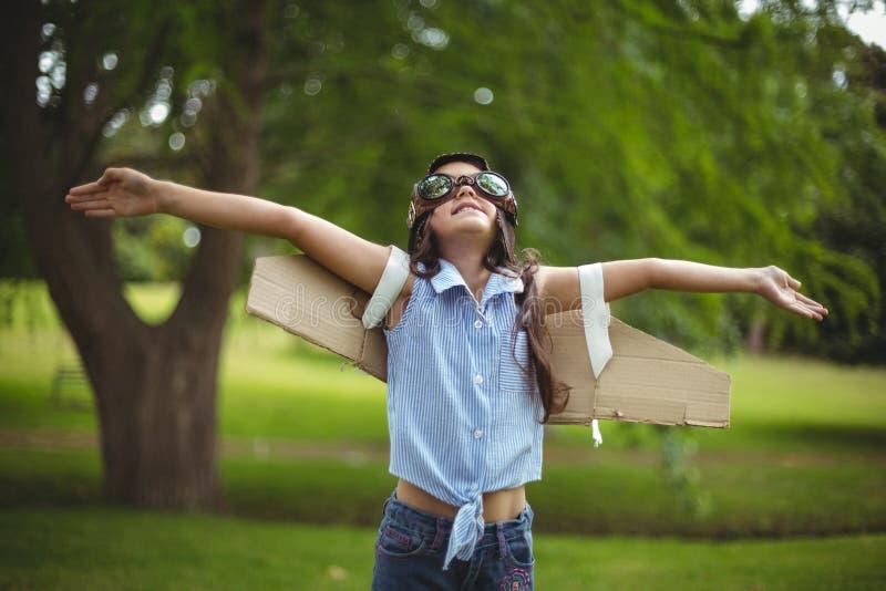 Ung flicka som låtsar för att flyga arkivfoton