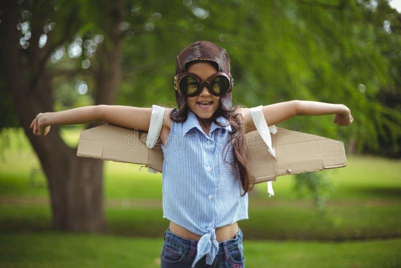 Ung flicka som låtsar för att flyga royaltyfri foto