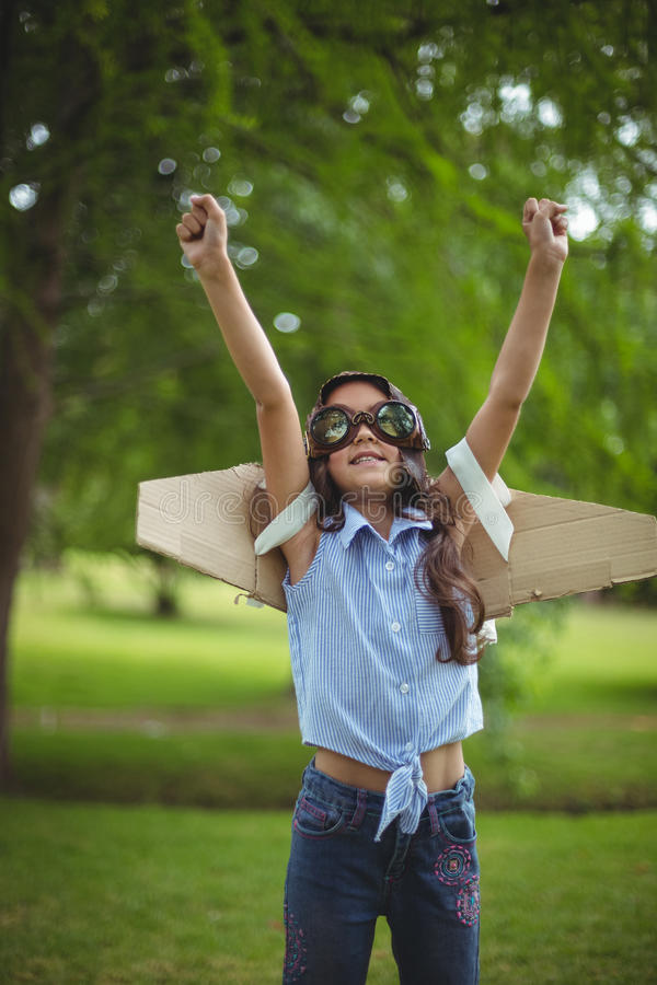 Ung flicka som låtsar för att flyga royaltyfri bild