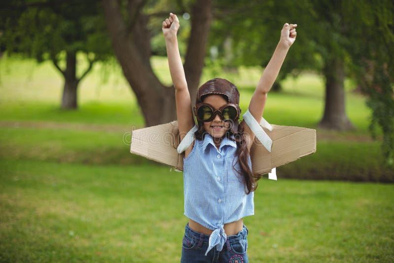 Ung flicka som låtsar för att flyga royaltyfri fotografi