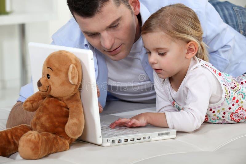 Ung flicka som leker med bärbar dator royaltyfri foto