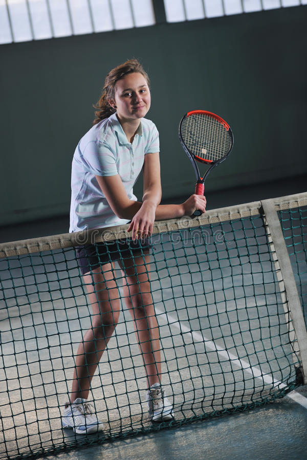 Ung flicka som leker modigt inomhus för tennis arkivfoton