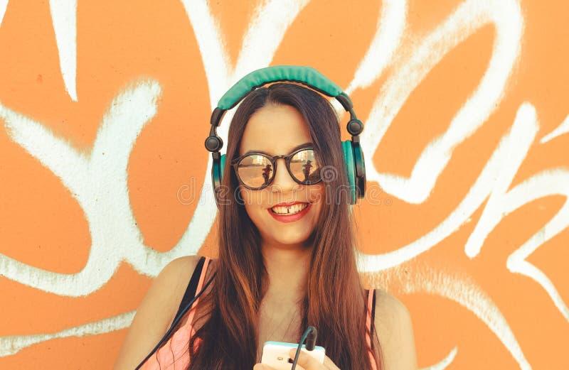 Ung flicka som ler och tycker om, medan lyssnar musik i hennes mobiltelefon royaltyfri fotografi
