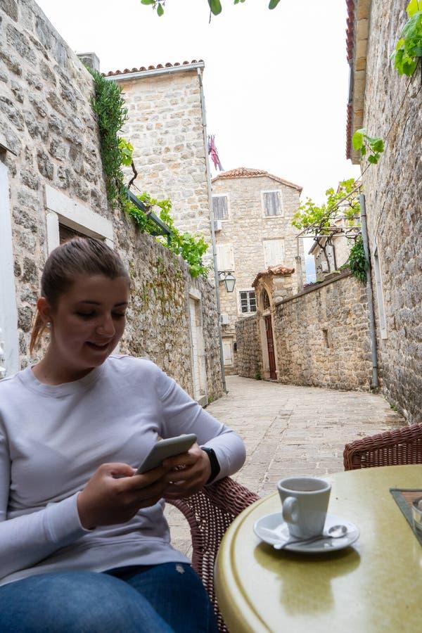 Ung flicka som ler skriva ett meddelande i smart telefonstund för att ta ett kaffe i en terrass av en smal gata för sten i Budva, royaltyfria bilder