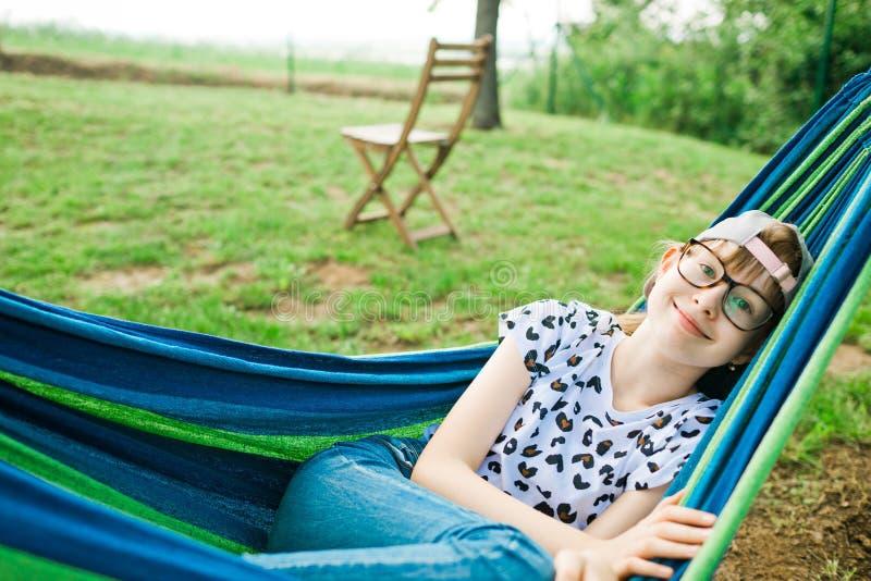 Ung flicka som ligger i h?ngmatta arkivfoton