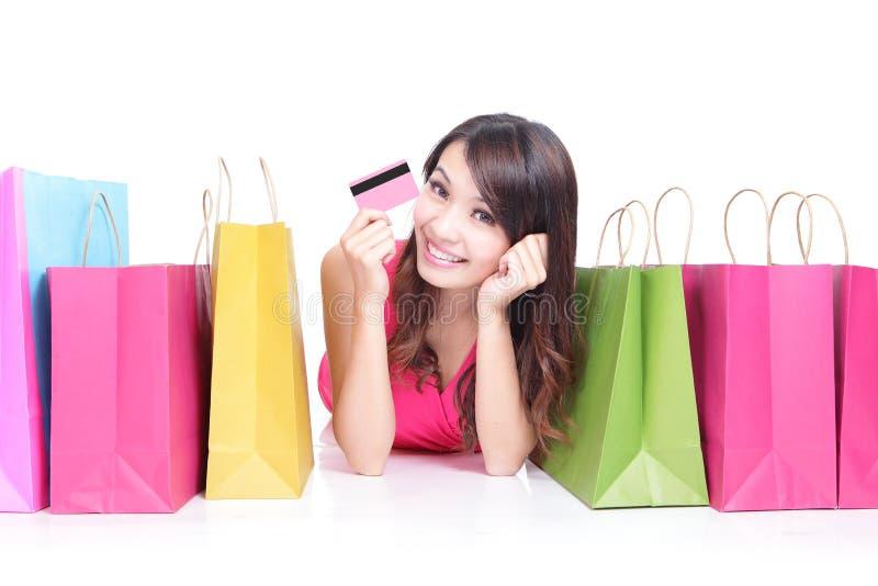 Ung flicka som ligger med shoppingpåsar royaltyfri fotografi