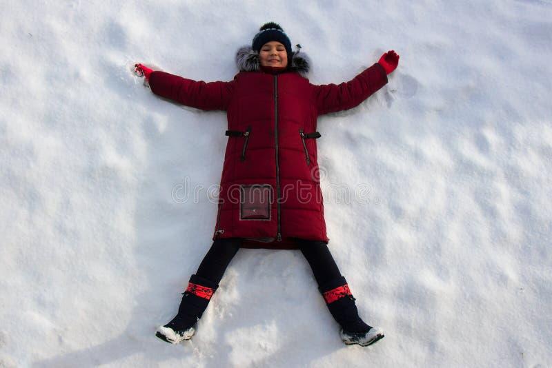 Ung flicka som ligger på den snövita snön arkivfoto