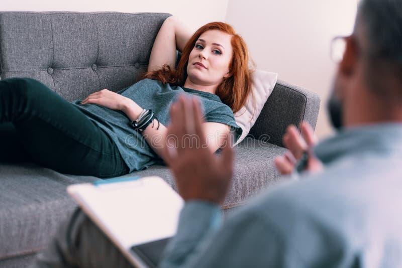 Ung flicka som ligger på en soffa, medan tala till hennes psykiater arkivbild