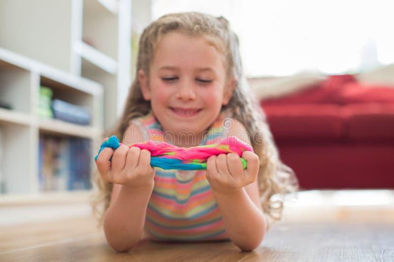 Ung flicka som ligger på golvet som spelar med färgrik slam royaltyfri foto