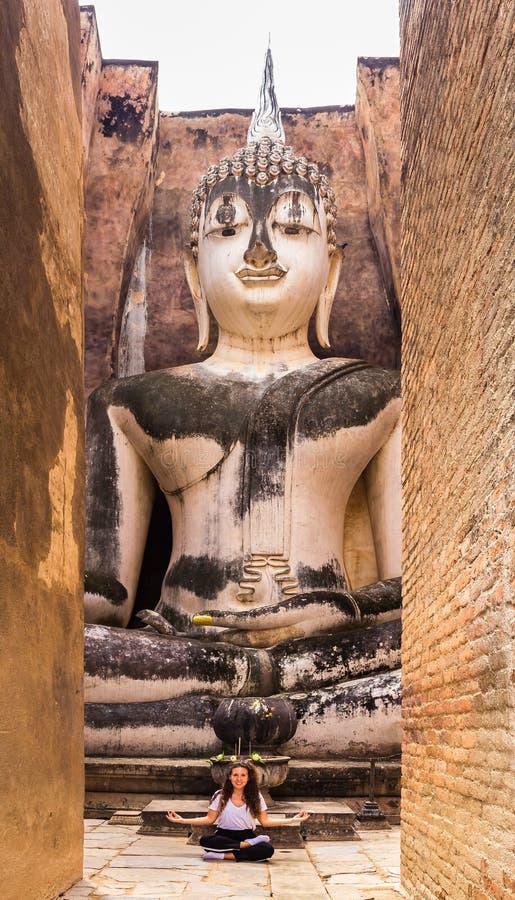 Ung flicka som mediterar i yogaposition i en buddistisk tempel arkivfoton