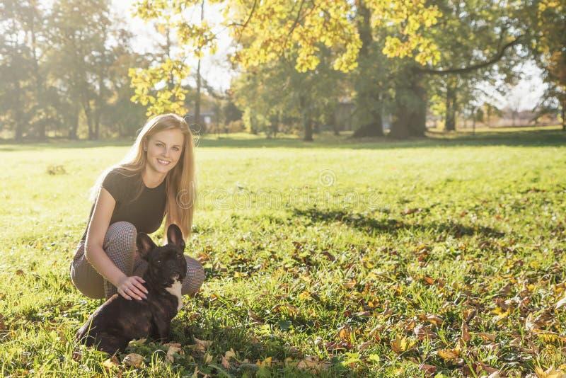 Ung flicka som pockar med franska Bulldog i höstparken royaltyfria foton