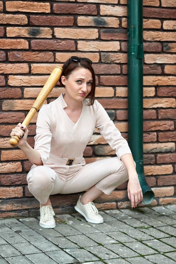 Ung flicka som poserar i bakgatan på tegelstenväggen som rymmer ett baseballslagträ arkivbild