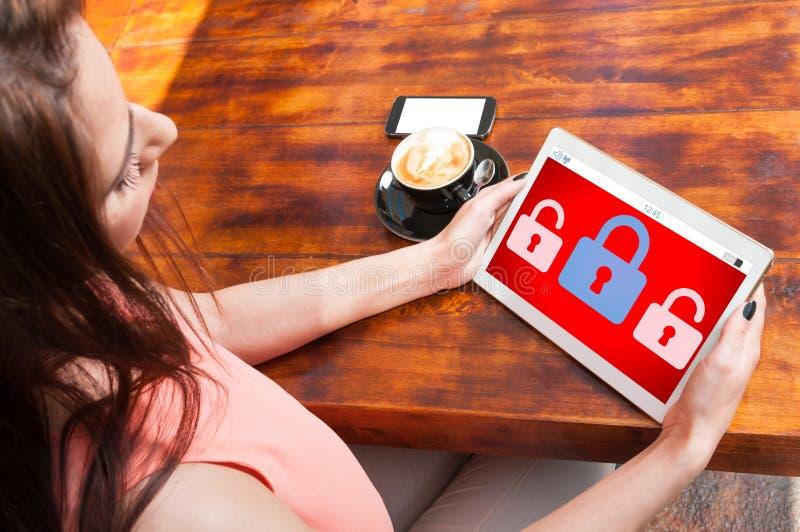 Ung flicka som rymmer den digitala minnestavlan med den låsta skärmen royaltyfria foton
