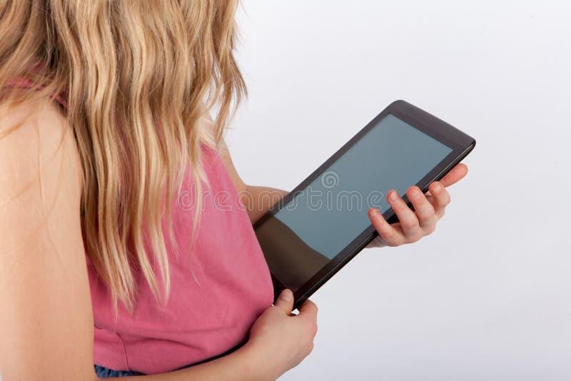 Ung flicka som rymmer en minnestavlaapparat med den tomma skärmen royaltyfria bilder