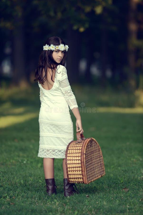 Ung flicka som rymmer en picknickkorg fotografering för bildbyråer