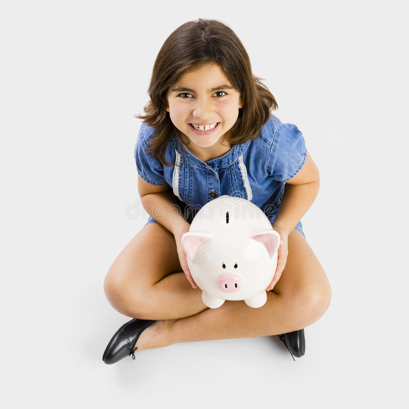 Ung flicka som rymmer en piggybank royaltyfria bilder