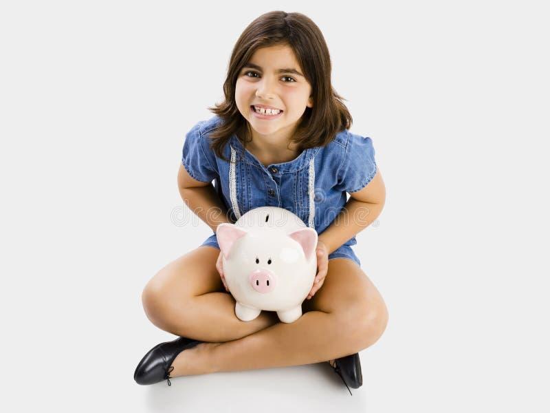 Ung flicka som rymmer en piggybank arkivfoto