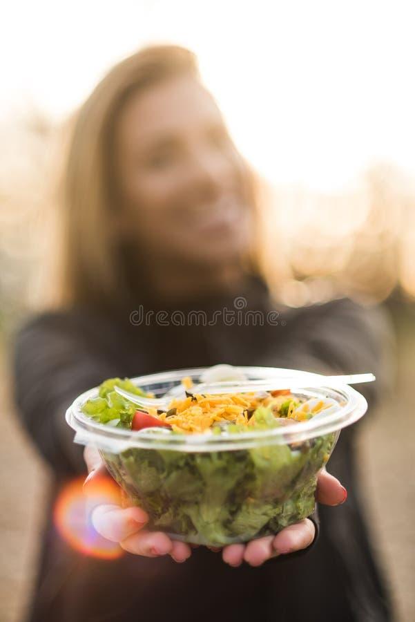 Ung flicka som rymmer en sallad på solnedgång royaltyfri foto