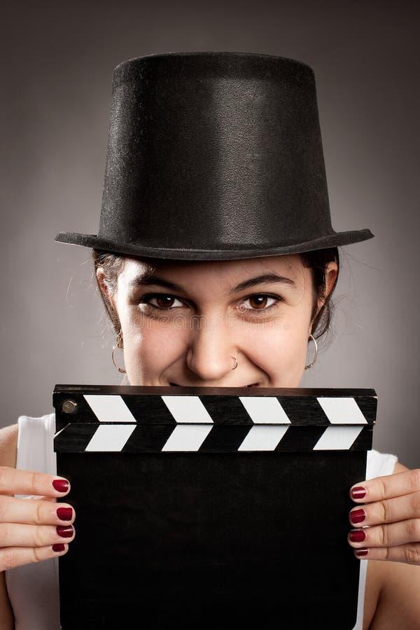 Ung flicka som rymmer ett filmclapperbräde arkivfoto