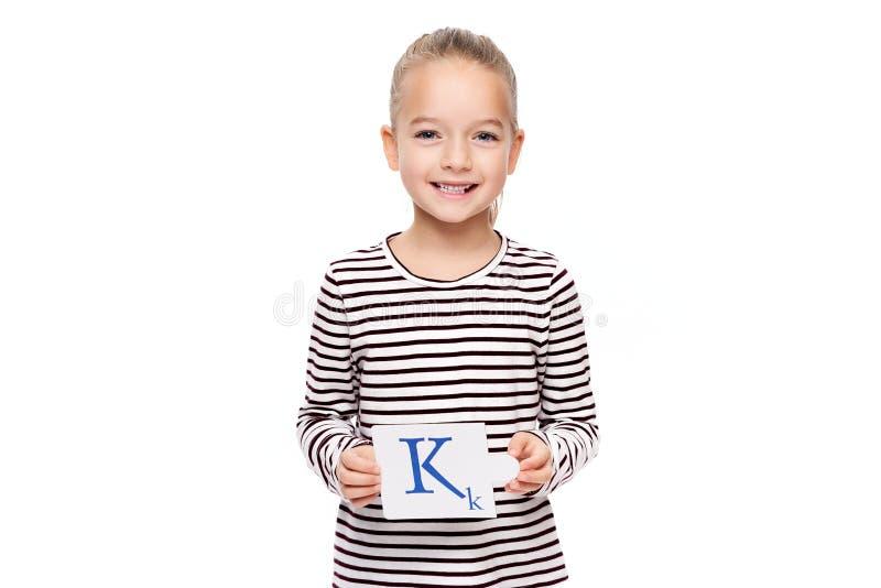 Ung flicka som rymmer ett kort med bokstav K Begrepp för anförandeterapi på vit bakgrund Korrekt uttal och artikulering royaltyfri fotografi