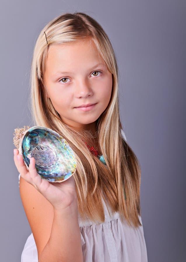 Ung flicka som rymmer ett snäckskal royaltyfri fotografi